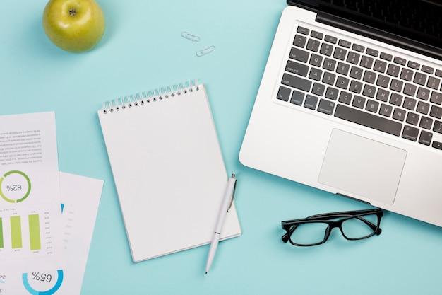 Groene appel, spiraalvormige blocnote, pen, oogglazen en laptop op blauwe achtergrond Gratis Foto
