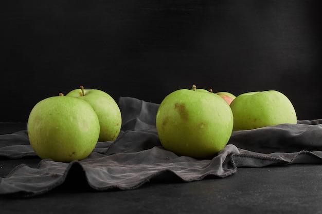 Groene appels geïsoleerd op zwarte achtergrond op grijs tafelkleed. Gratis Foto