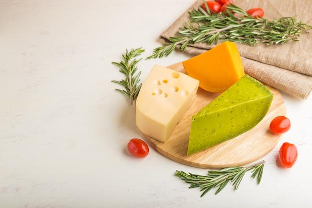 Groene basilicumkaas en verschillende soorten kaas met rozemarijn en tomaten Premium Foto
