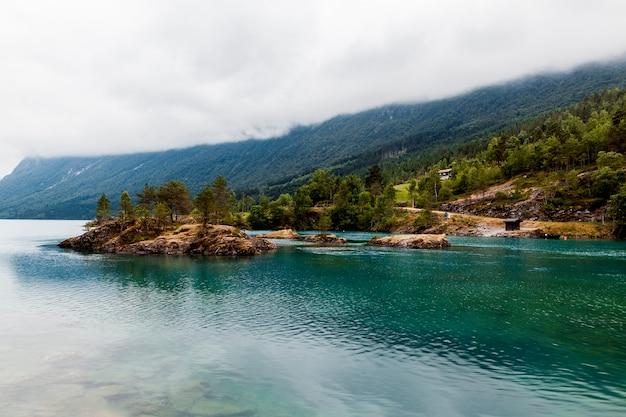Groene berg over het blauwe idyllische meer Gratis Foto