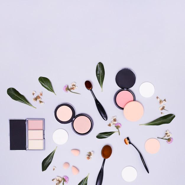 Groene bladeren en bloemen met ovale zwarte borstels; blender spons; compact poeder en oogschaduwpalet op purpere achtergrond Gratis Foto
