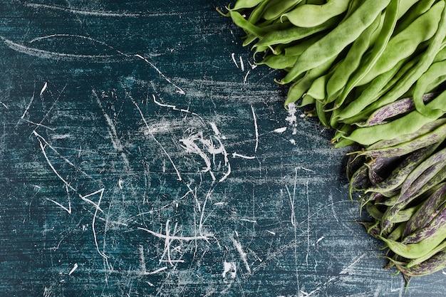Groene bonen geïsoleerd op blauwe tafel. Gratis Foto