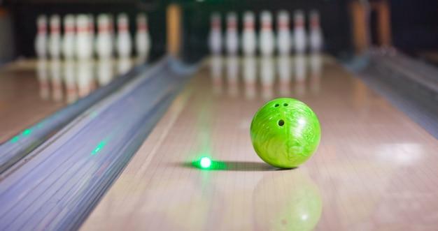 Groene bowlingbal zetten steegje met wazig bowling pin Premium Foto