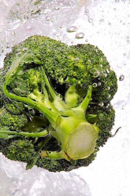 Groene broccoli in water laten vallen Gratis Foto