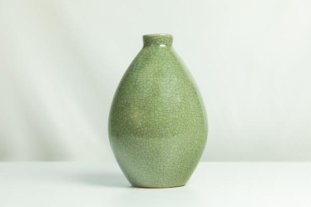 Groene ceramische vaas die op wit wordt geïsoleerd Premium Foto