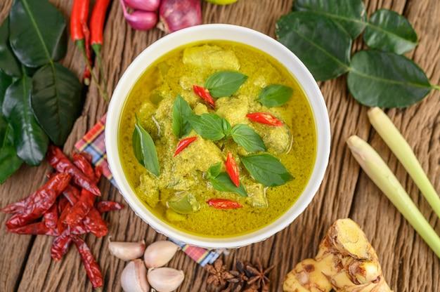 Groene curry in een kom met limoen, rode ui, citroengras, knoflook en kaffir limoenblaadjes Gratis Foto