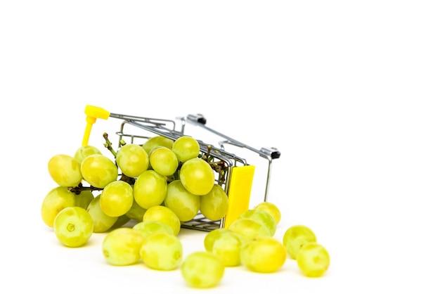 Groene druiven in een miniatuurboodschappenwagentje op een wit geïsoleerde achtergrond. druiven kopen. kopieer ruimte. Premium Foto