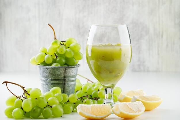 Groene druiven met plakjes citroen, druiven cocktail in een mini-emmer op witte ondergrond Gratis Foto