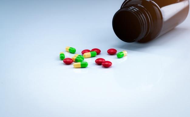 Groene en gele capsules met rode tablettenpillen dichtbij bruine drugfles op witte achtergrond. farmaceutische industrie. pijnstiller medicijn. Premium Foto