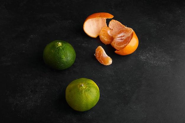 Groene en gele mandarijn sinaasappelen op zwarte achtergrond, bovenaanzicht. Gratis Foto