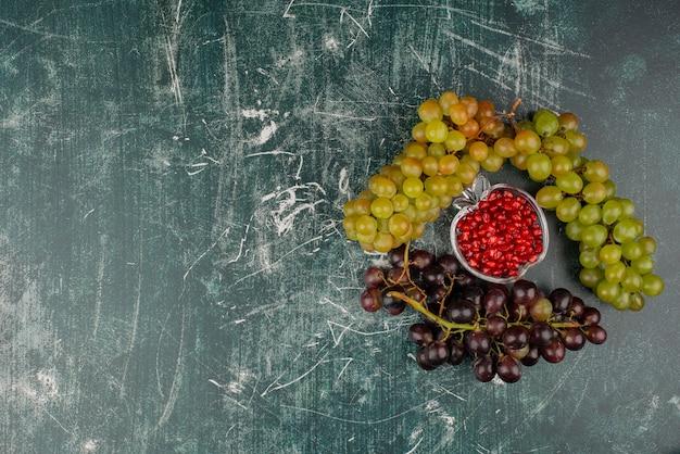 Groene en zwarte druiven met granaatappelzaden op marmeren oppervlak. Gratis Foto