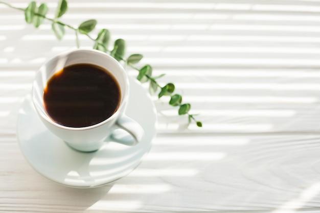 Groene eucalyptustak en smakelijke kop van koffie op wit houten bureau Gratis Foto