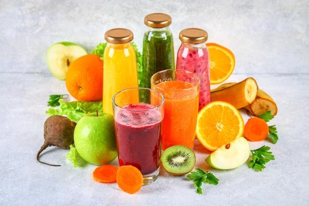 Groene, gele, paarse smoothies in bessenflessen, peterselie, appel, kiwi, sinaasappel op een grijze tafel. Premium Foto