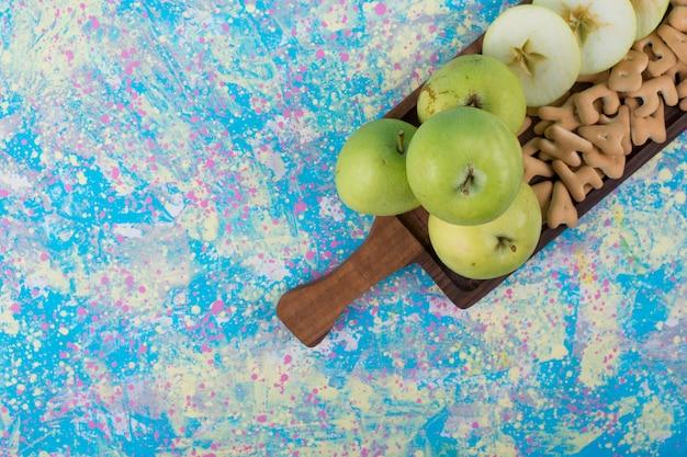 Groene gesneden appels met crackers op het houten bord in de bovenhoek. Gratis Foto