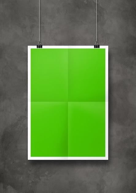 Groene gevouwen poster die met clips aan een betonnen muur hangt. Premium Foto