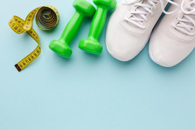 Groene gewichten witte sneakers en meter Gratis Foto