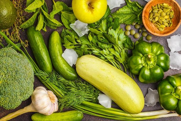 Groene groenten op een donkere ondergrond. plantaardige veganistische dieetvoeding: courgette, paprika, broccoli, komkommers, avocado, appel, kruiden. gezond levensstijlconcept. Premium Foto