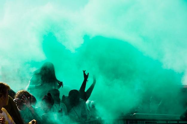 Groene holi-kleurpoeder over de menigte Gratis Foto