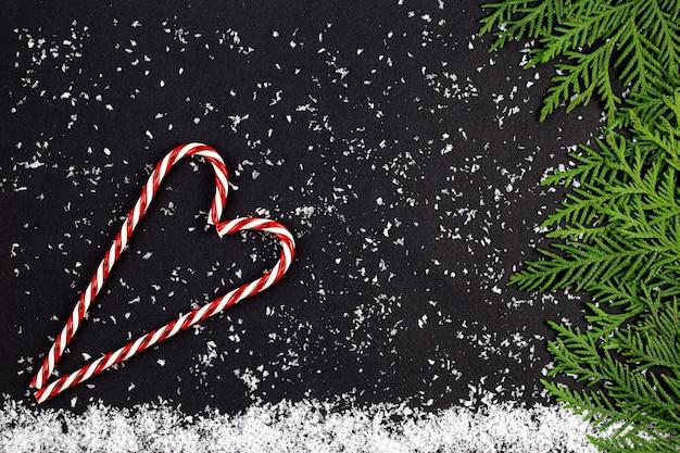 Groene kerstboom gemaakt van naaldhout takken en sneeuwvlokken op een donker Premium Foto