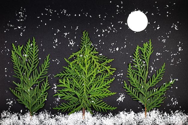 Groene kerstboom gemaakt van naaldhout takken op een donkere achtergrond. minimale compositie achtergrond. nieuwjaar en kerstmis concept. Premium Foto