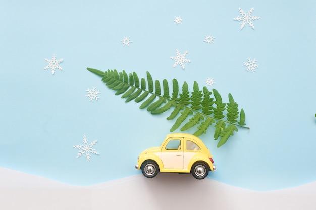 Groene kerstboom op gele speelgoedauto met sneeuwvlokken Premium Foto