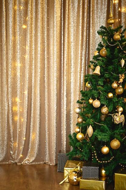 Groene kunstmatige fir kerstboom in de gouden kamer met lichtslingers versierd met gouden ballen, kralen en speelgoed. Premium Foto