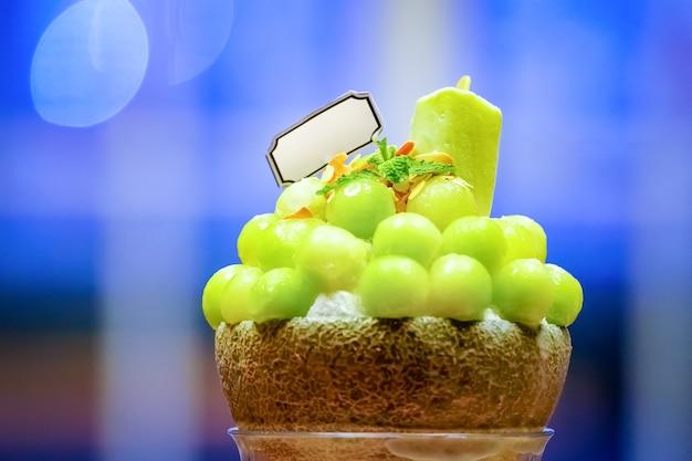 Groene meloenbolvorm is gerangschikt op de bovenkant van bingsu (koreaanse ijsstijl) en versierd met groene thee-ijs en muntblad op de houten plaat en gezoete gecondenseerde melk ernaast. Premium Foto