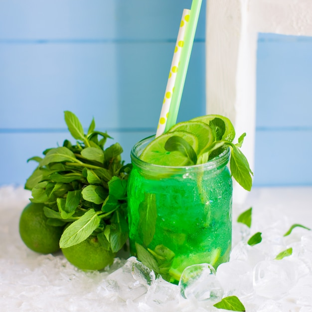 Groene mojito geserveerd in glazen pot gegarneerd met limoen en munt Gratis Foto