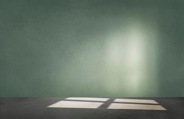 Groene muur in een lege ruimte met betonnen vloer Gratis Foto