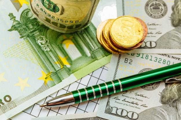 Groene pen legt op dollarbiljetten in de buurt van de gouden munten op de tafel. Premium Foto