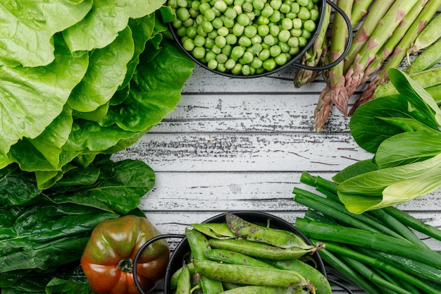 Groene peulen, erwten in pannen met asperges, tomaat, zuring, spinazie, sla, groene ui bovenaanzicht op een houten muur Gratis Foto