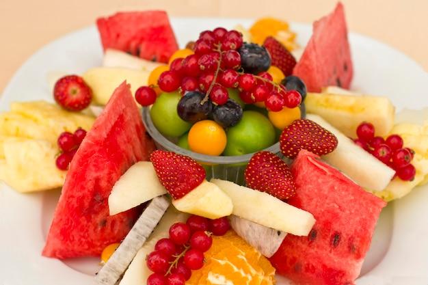 Groene pruim, rode bes, bosbes, aardbei, physalis, pitahaya, watermeloen Premium Foto