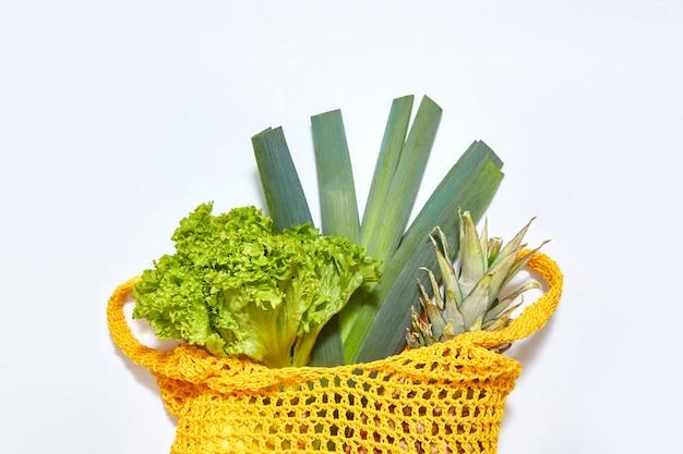 Groene salade en vruchten in de gele zak van het ecokoord op witte achtergrond. het uitzicht vanaf de top. plat leggen met kopie ruimte. Premium Foto