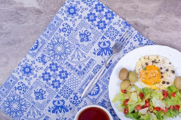 Groene salade met gebakken ei en een kopje thee Gratis Foto
