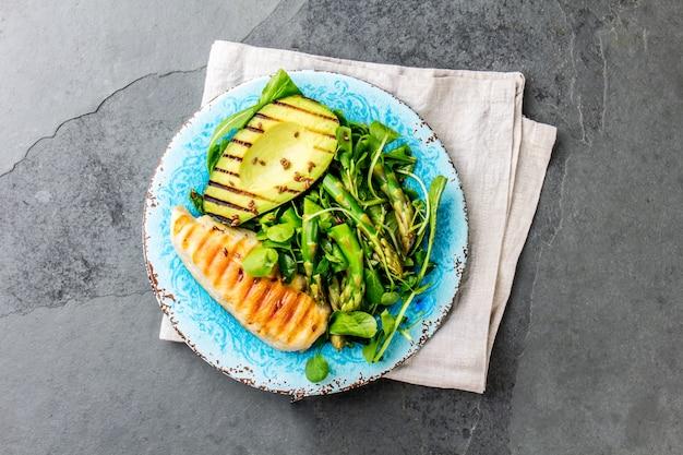 Groene salade met gegrilde avicado en gegrilde kip Premium Foto