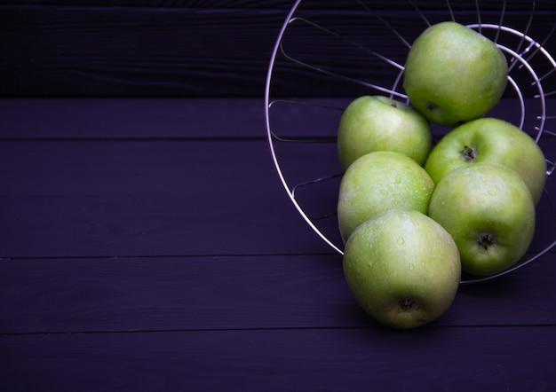 Groene sappige appels met waterdruppels op donkere achtergrond. gratis exemplaarruimte. Premium Foto