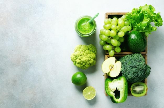 Groene smoothie in glazen pot met verse biologische groene groenten en fruit op grijs. lente dieet, gezonde rauwe vegetarische, veganistische concept, detox ontbijt, alkalisch schoon eten. ruimte kopiëren Premium Foto