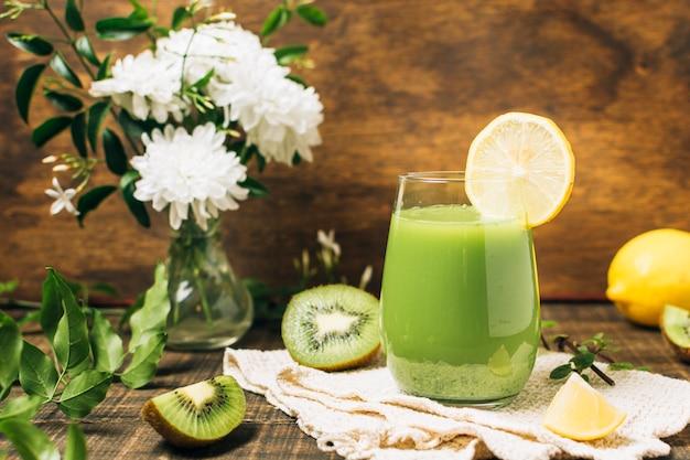Groene smoothie naast vaas met bloemen Gratis Foto