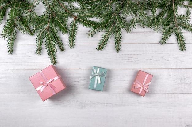 Groene sparren takken en roze geschenkdozen op witte houten achtergrond. kerst concept met kopie ruimte Premium Foto