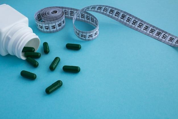 Groene tabletten en witte centimeter op het blauw Premium Foto