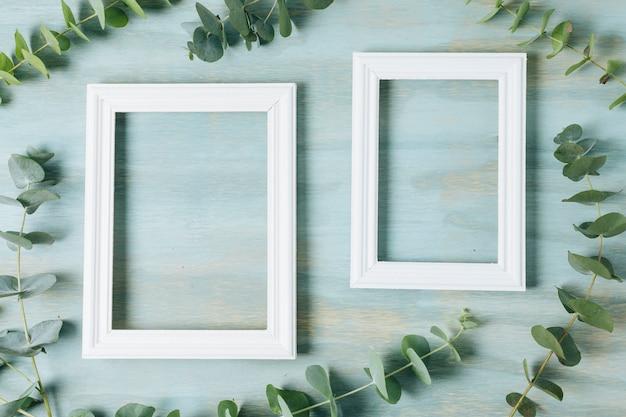 Groene takjebladeren rond het witte grenskader op blauwe textuurachtergrond Gratis Foto