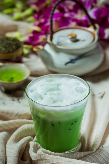 Groene thee iced in een hoog glas met room gegarneerd met iced groene thee gedecoreerd met groene theepoeder. Gratis Foto