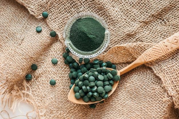 Groene zeewier spirulina in tabletten en poeder op een juteachtergrond. bovenaanzicht Premium Foto