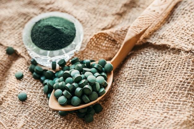Groene zeewier spirulina in tabletten en poeder op een juteachtergrond. plantaardige proteïne. kopieer de ruimte Premium Foto