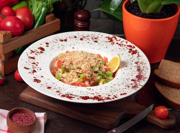 Groente, tomaten, komkommersalade met crackers. salade op de keukentafel in witte plaat Gratis Foto