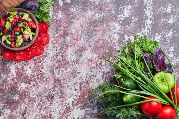 Groentemix geïsoleerd op een stuk marmer met een kopje salade opzij Gratis Foto