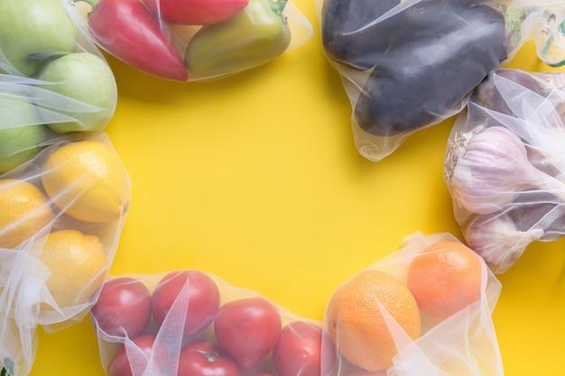 Groenten en fruit op herbruikbare zakken frame achtergrond Premium Foto