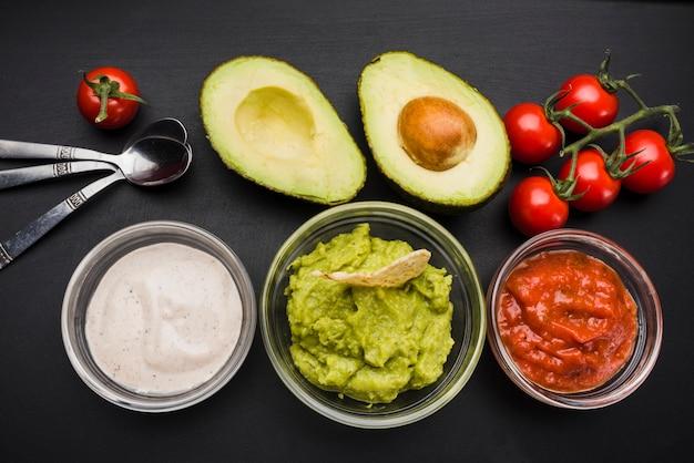 Groenten en set van sauzen in kommen in de buurt van lepels Gratis Foto