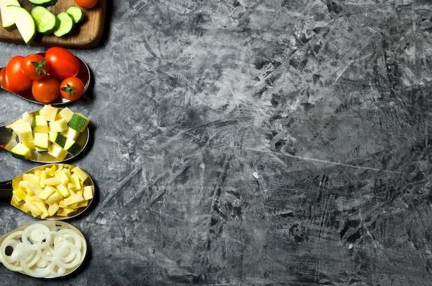 Groenten. verse groenten (komkommers, tomaten, uien, knoflook, dille, sperziebonen) op een grijze achtergrond. bovenaanzicht copyspace Premium Foto