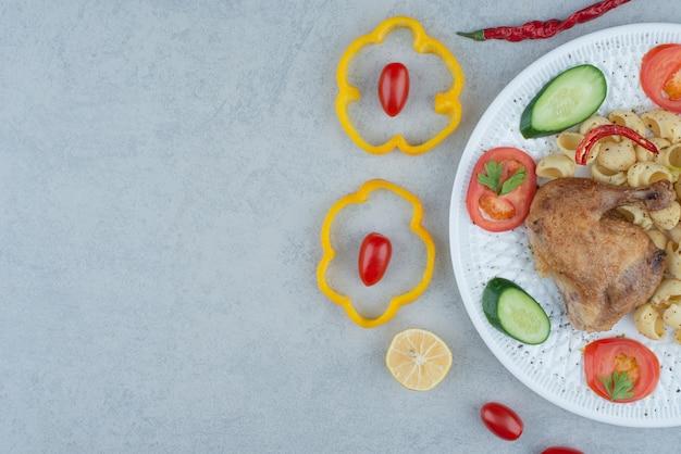 Groentensalade op witte plaat met deegwaren en kip op marmeren achtergrond Gratis Foto